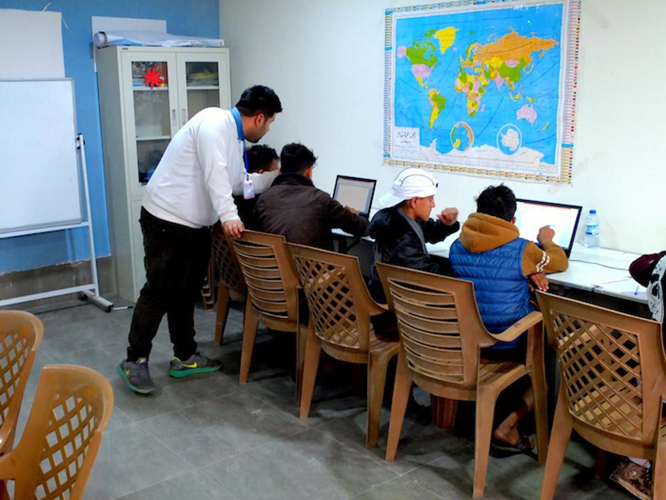 Young people learn valuable skills in a computer class  at Debaga camp in Iraq's Erbil Governate.