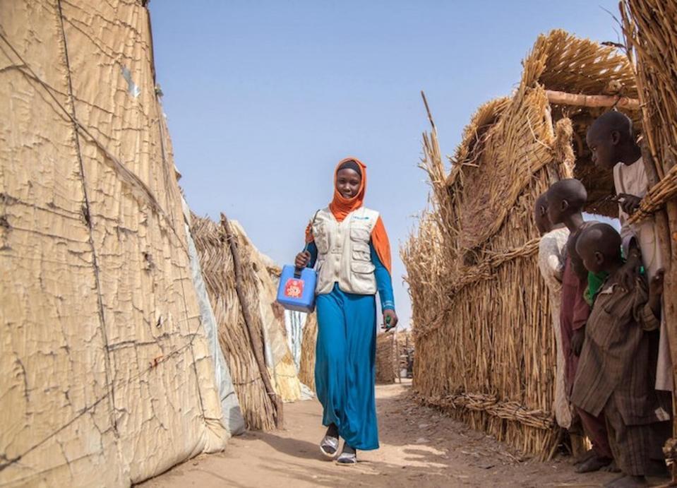 Aisha Mohammed, seorang pemberi vaksinator tim polio yang didukung UNICEF, berjalan melalui kamp Muna Garage untuk para pengungsi internal di Maiduguri, Negara Bagian Borno, Nigeria pada Januari 2018.