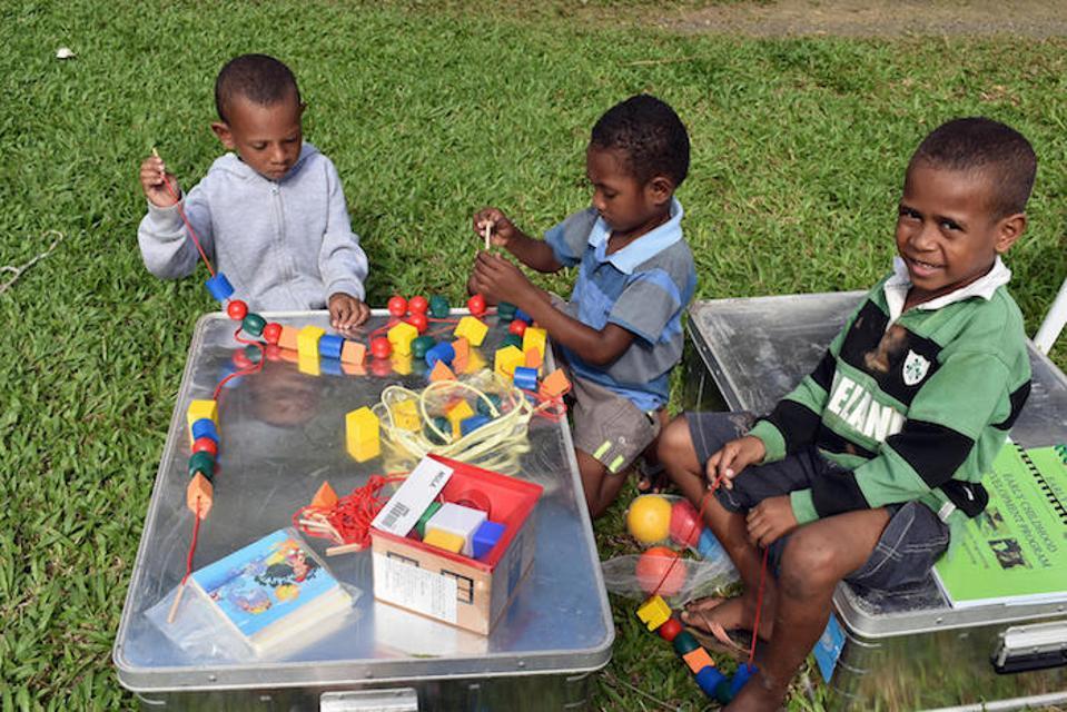 Anak-anak muda di Alatau, Provinsi Teluk Milne, Papua Nugini mengeksplorasi isi dari paket School-in-a-Box yang didistribusikan oleh UNICEF ke 12 Pusat Pembelajaran Awal sebagai bagian dari program Pengembangan Anak Usia Dini yang Inklusif.