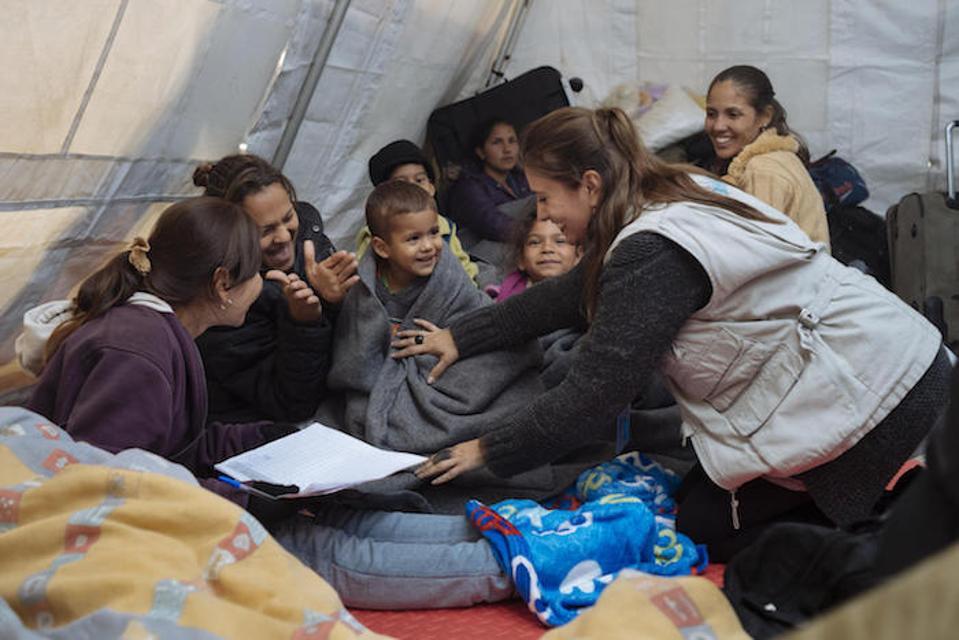 Maria Belen Rodriguez, seorang pejabat UNICEF Ekuador, membagikan selimut termal untuk wanita dan anak-anak Venezuela di Rumichara di perbatasan Kolombia-Ekuador pada Agustus 2018.