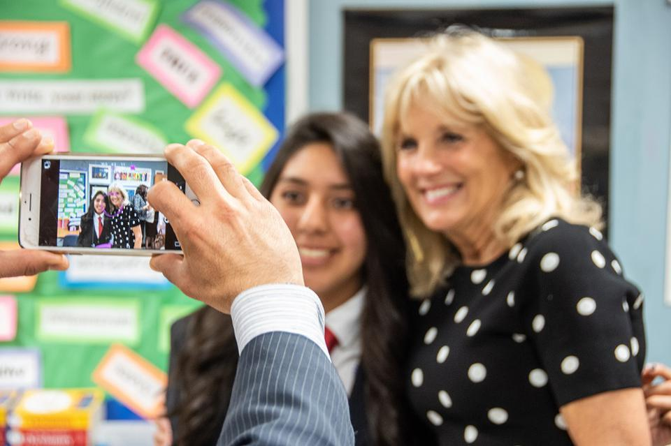 Dr. Jill Biden takes a photo with a student.