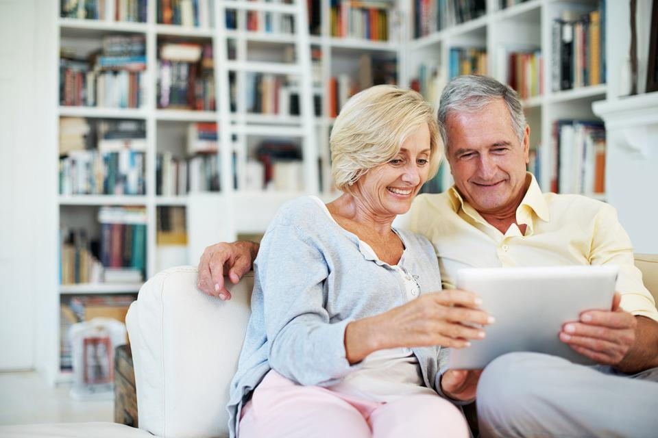 Couple on sofa looking at tablet