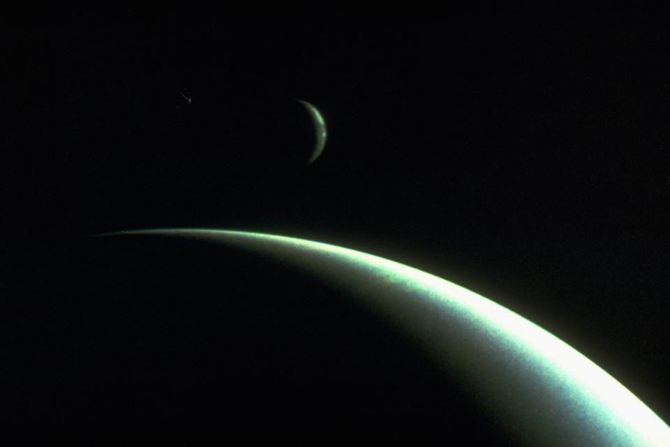 The planet Neptune and its largest moon Triton, as photographed by Voyager 2.
