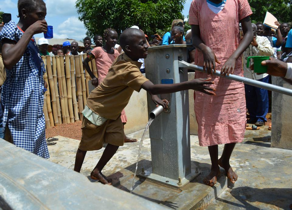 Children in Guinea gather water from a UNICEF-installed water pump in N'Zerekore.