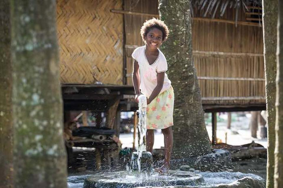 A young girl pumps water from an underground well in A young girl pumps water from an underground well in Papua New Guinea. A little over a year ago, a 7.5 magnitude earthquake hit the region, destroying public infrastructure and disrupting the water supply.