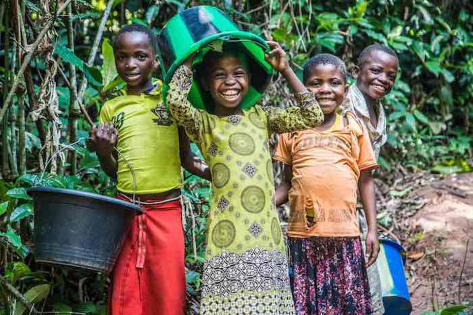 Children clown around while collecting water at a water station UNICEF built in the Democratic Republic of Congo (DRC).