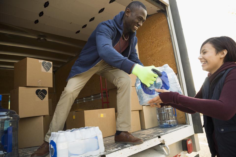 Smiling volunteers unloading water bottles on truck