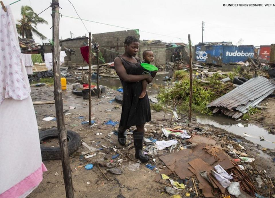 Cecilia Borges carries her son, Fernandino, through the destroyed informal settlement, in Beira, Mozambique, on 20 March 2019.