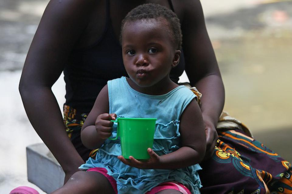 A little girl sits on her mother's lap at a secondary school in Mozambique now being used to shelter evacuees from Cyclone Idai.