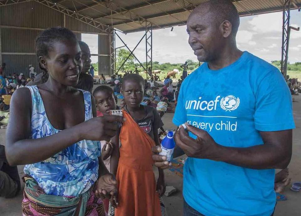 In Malawi, UNICEF WASH officer Alan Kumwenda shows Anne Joseph how to use a water purifying solution to keep her family's drinking water clean and safe.