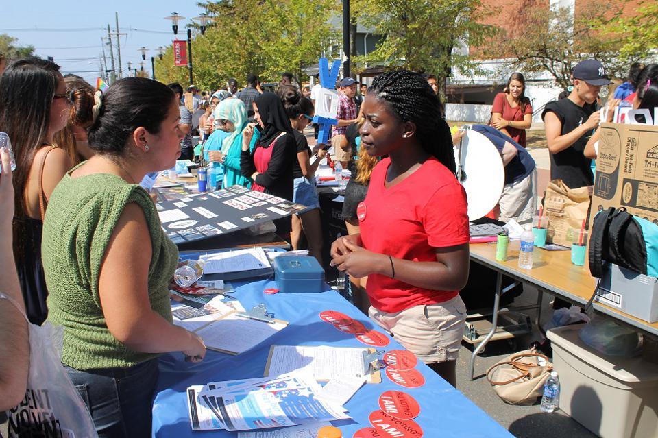 College students register their peers to vote on campus.