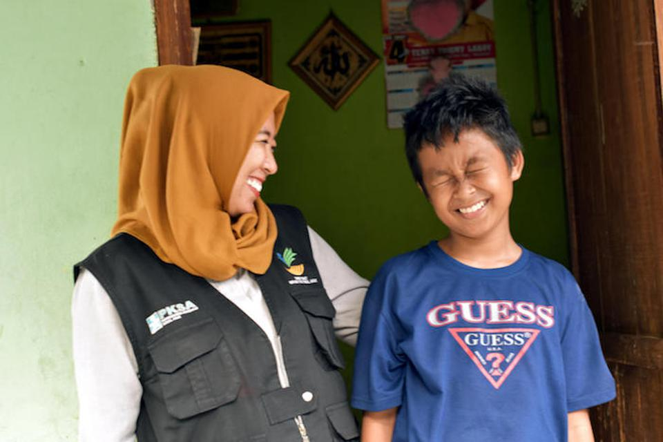 UNICEF-supported social worker Chi Ramadhani stands with Rivaldi, 13, outside his family home in Palu, Central Sulawesi. Ramadhani was the social worker who reunited Rivaldi with his family.
