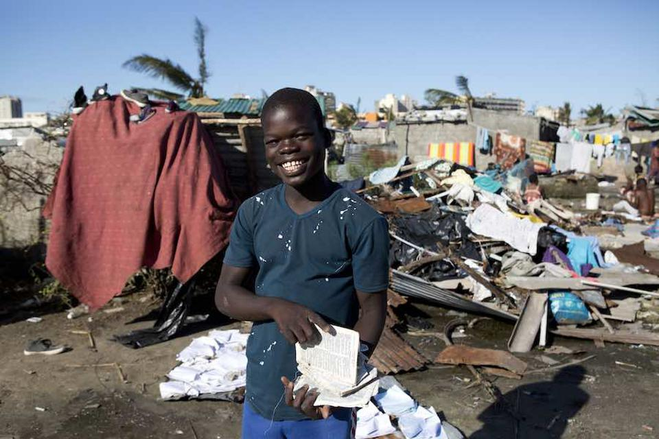 On March 24 in Mozambique, Caelono, 15, holds pages from a schoolbook he rescued when the floodwaters receded near his home in Beira.