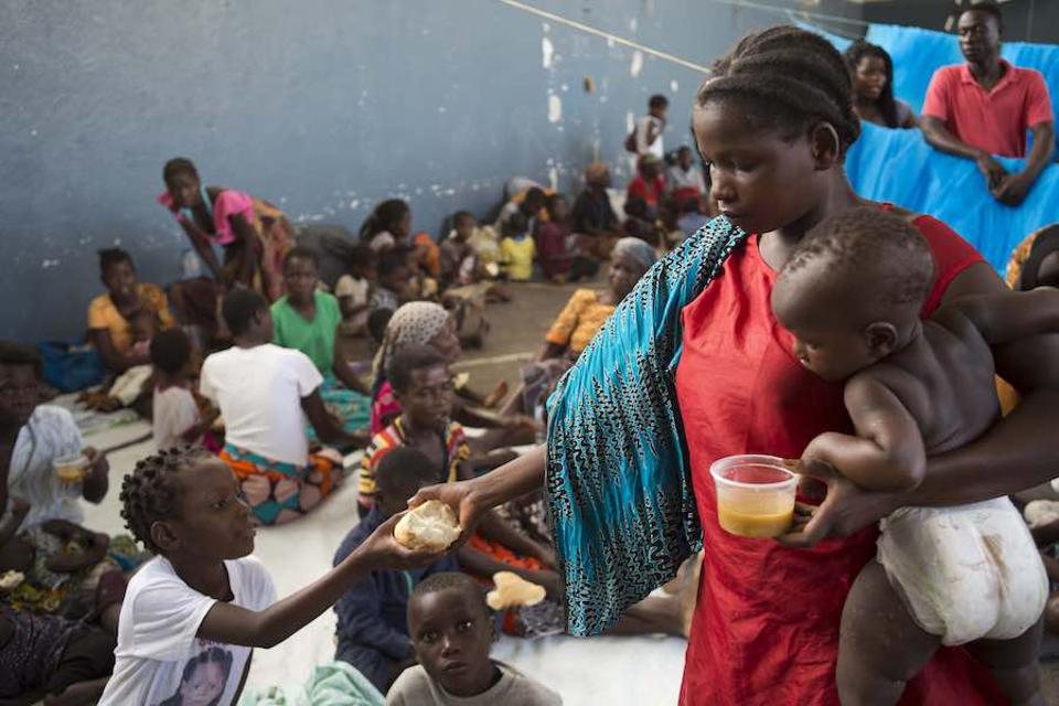In Buzi, Mozambique, children receive food donated by a supermarket chain at the Samora Machel school where they were brought after their homes were destroyed and flooded.