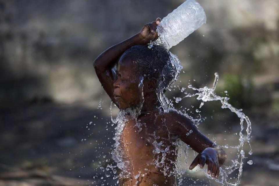 On March 24 in Mozambique, a child washes himself with dirty water in an area that was flooded after Cyclone Idai made landfall in Beira.