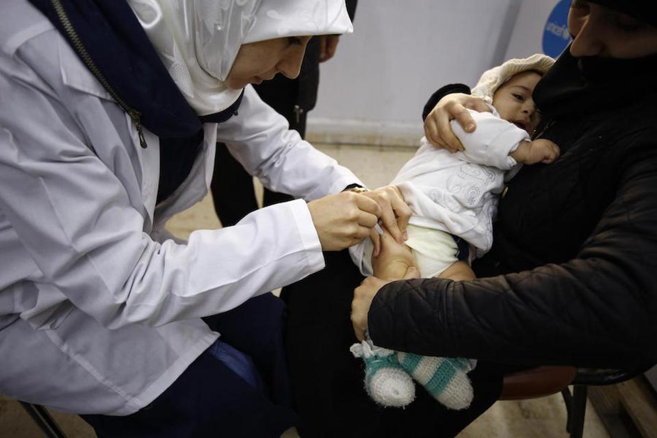 An infant is vaccinated in December 2018 at the Eastern Douma Primary Health Center in Syria, operated by the local department of health with support from UNICEF.