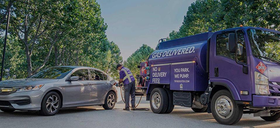 A Booster Fuels truck fills up a car.