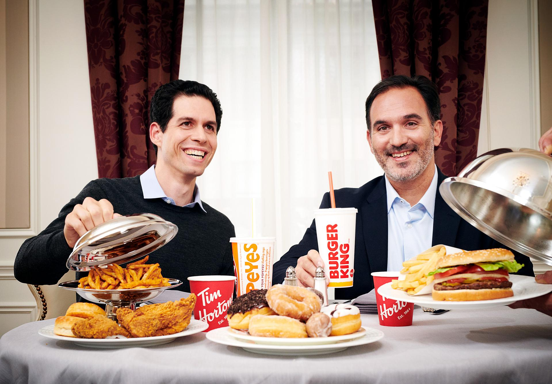 Photo of Daniel Schwartz and Jose Cil seated at a table with fast food.