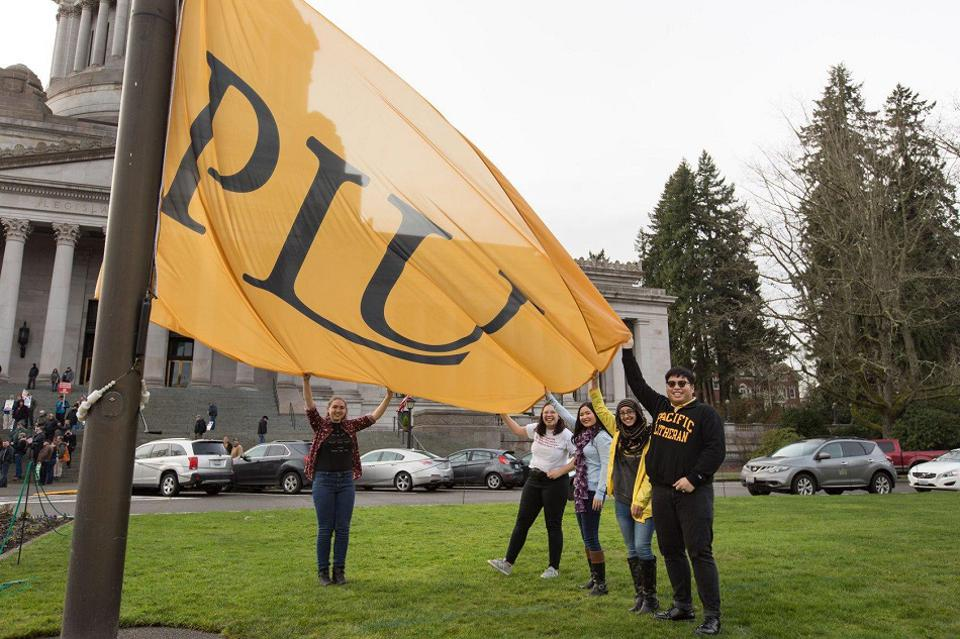 Students hold the PLU flag