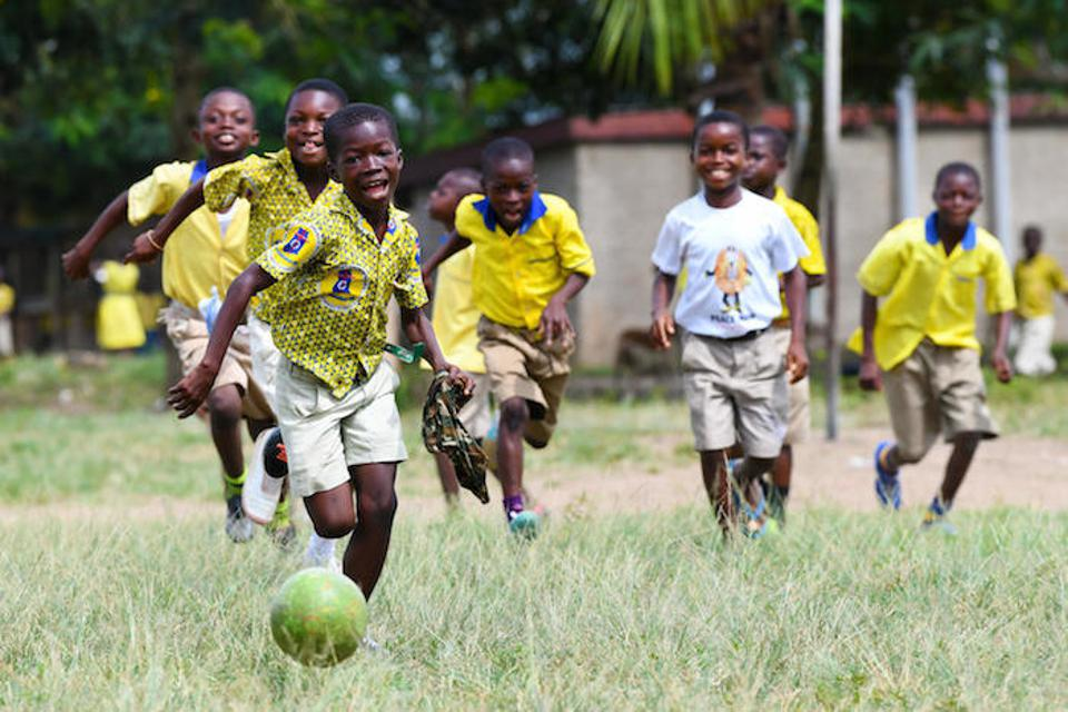 Boys playing football outside at the Asuokaw Methodist School in the Eastern Region in Ghana.