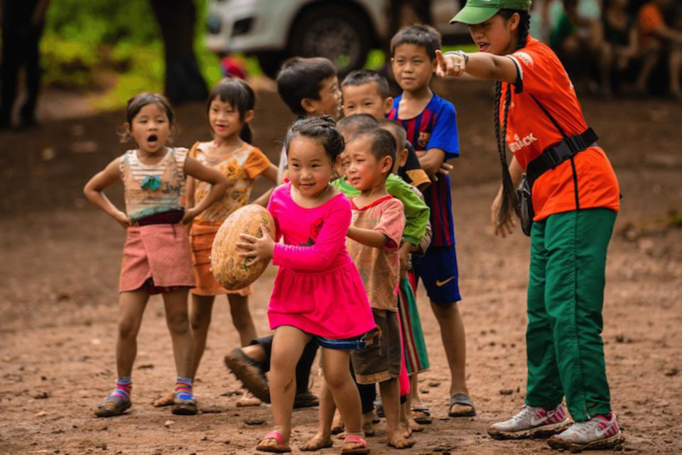 A coach teaches young players teamwork and other life skills through sport in a village in northern Laos.