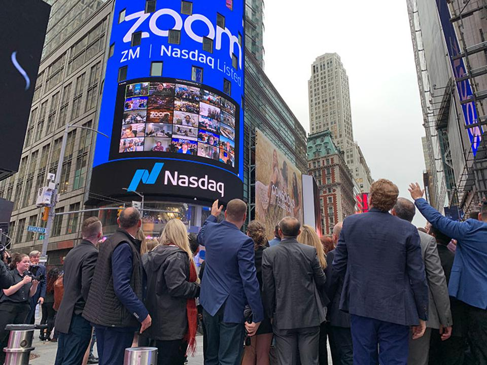 Zoom executives wave to employees via Zoom on Nasdaq's tower on the day of its IPO.