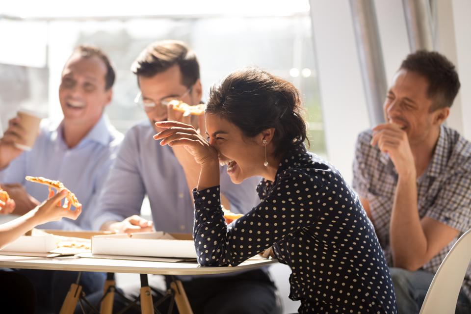 Indian woman laughing eating pizza with diverse coworkers in office