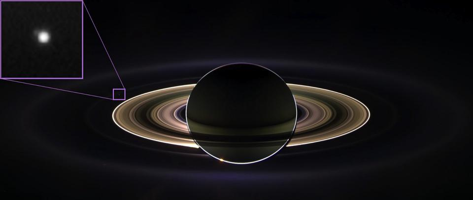 A backlit Saturn as viewed from NASA's Cassini spacecraft. Earth is visible as well.