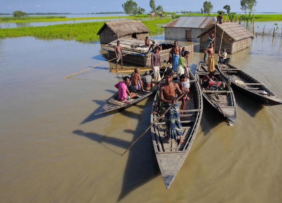 A family takes to their boats after severe flooding in 2017 in the northern district of Kurigram, Bangladesh.