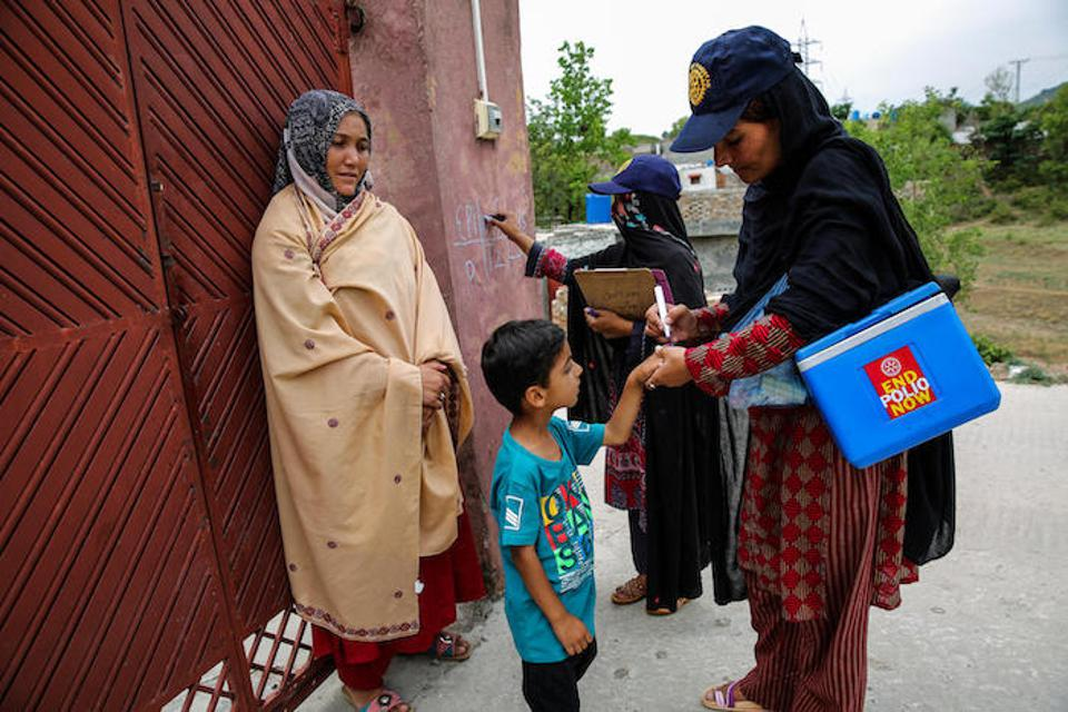 Female frontline health workers go door-to-door to vaccinate children against polio in Islamabad, Pakistan in May 2017.