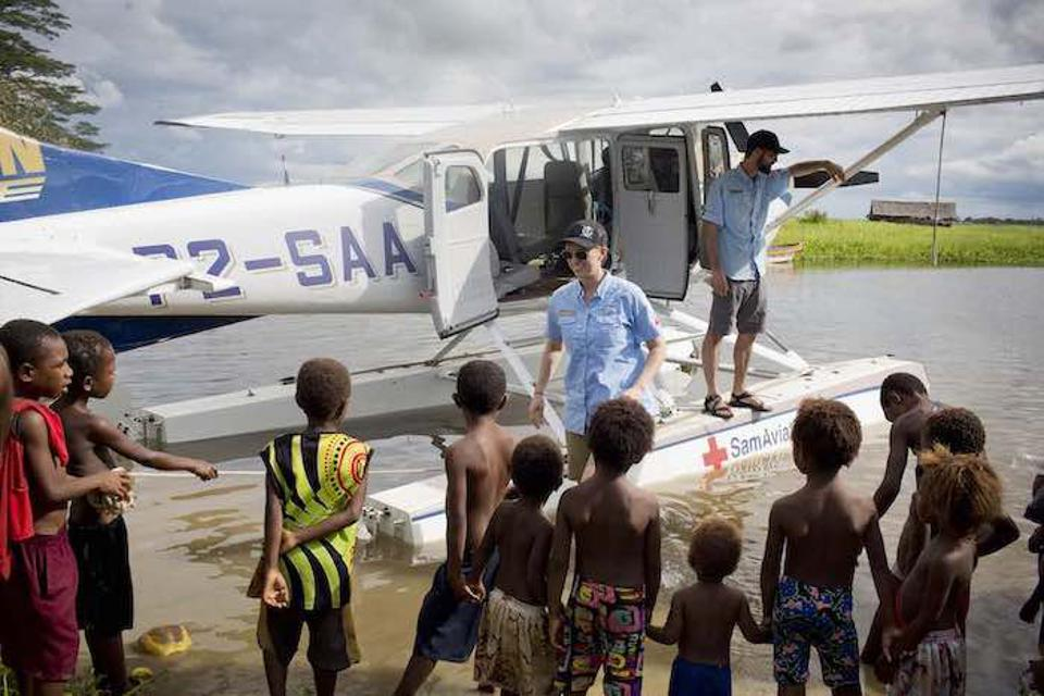 Tracy Hamer, a pilot with Samaritan Aviation, meets local children in Angoram, East Sepik Province, Papua New Guinea, where UNICEF is working to eliminate the threat of maternal and neonatal tetanus (MNT) through lifesaving vaccines.