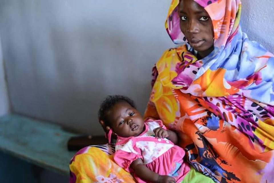 A mother and child wait to be vaccinated in Chad in February 2016.