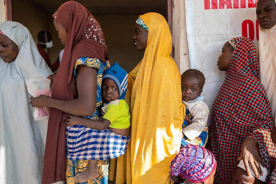 Mothers and children line up for vaccinations and health care at a UNICEF-supported mobile health clinic in Farankasa village, Zamfara State, Nigeria in November 2018.