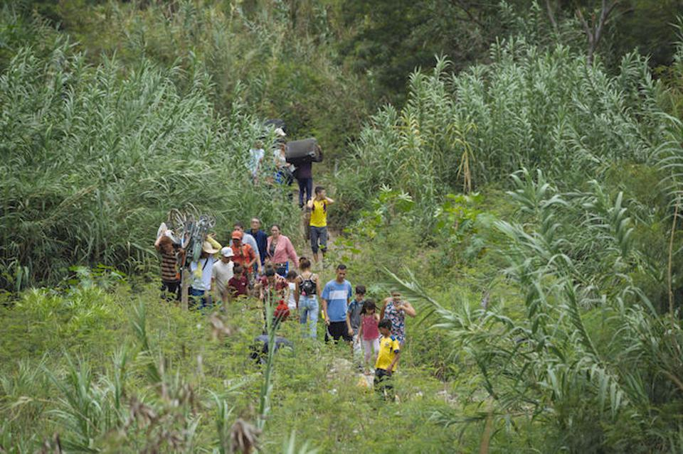 On April 23, 20109 in Cucuta, Colombia, a group of migrants crosses an illegal path next to the bridge connecting Colombia and Venezuela.