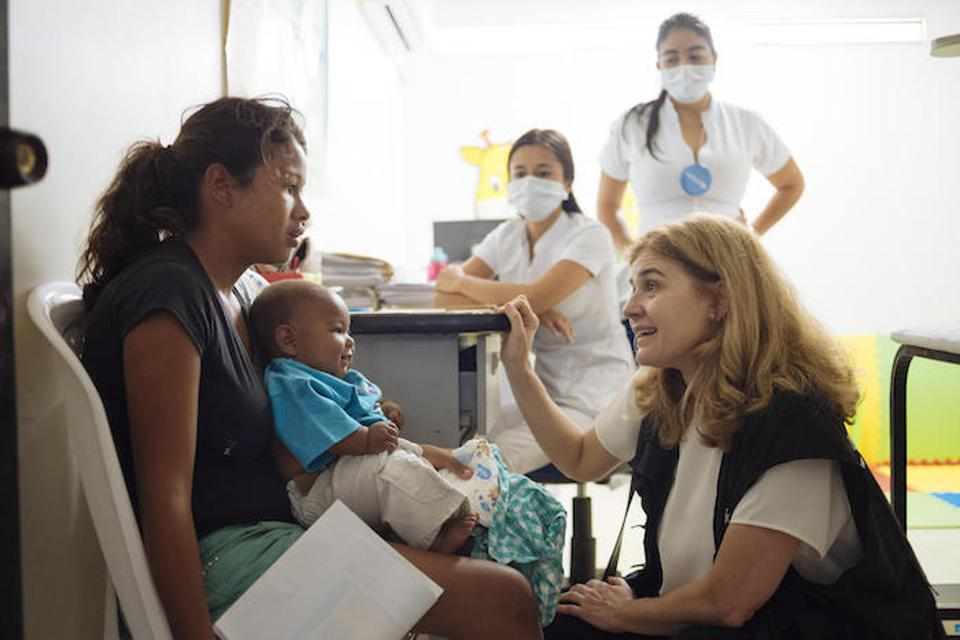 On April 23, 2019 in Cucuta, Colombia, UNICEF Director of Communications Paloma Escudero speaks with a woman and her child at the UNICEF-supported health center.