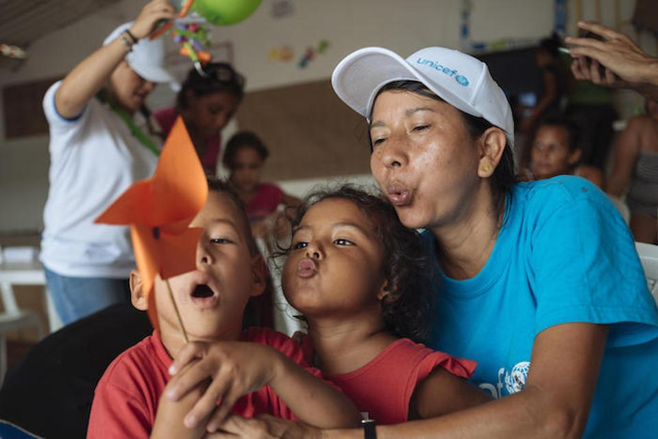 On April 25, 2019, volunteer Pureza Peña (far right) plays with children from Venezuela during a workshop at a Child-Friendly Space in Cucuta, Colombia, where UNICEF provides learning activities for Venezuelan migrant children and their parents. The program is supported by UNICEF in coordination with OIM and the Colombian Chancellery.
