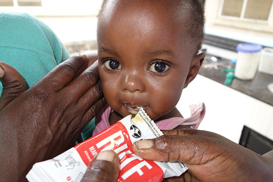 A malnourished child tries a meal of ready-to-use therapeutic food from MANA.