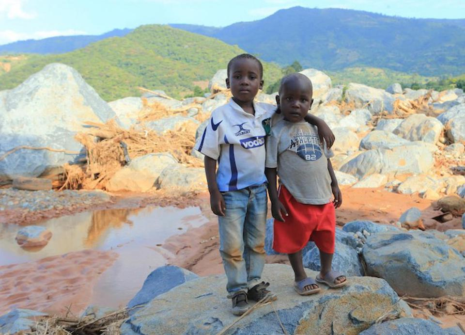 Brothers Anesu Mupfute (left) and Future Gore stand near the spot where their house was swept away when Cyclone Idai hit Coppa in Risitu Valley Chimanimani, Zimbabwe in March 2019. The boys lost both parents in the storm.