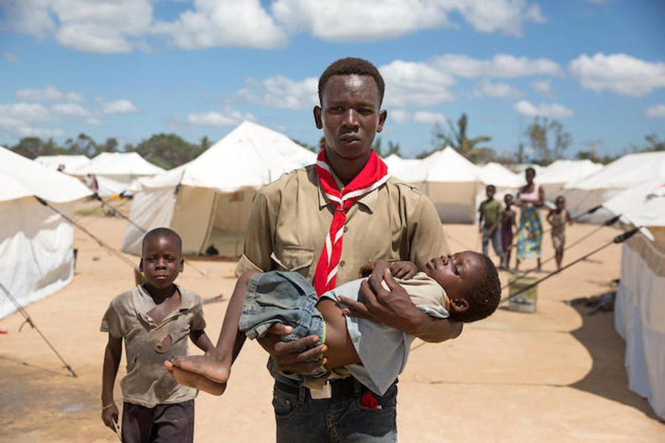 On April 5 in Dondo, Mozambique, volunteer social mobilizer Lucio Carlos carried Luisa Daniel, 5, suffering from fever and vomiting, to a medical tent in a UNICEF-supported accommodation center, where she was tested for malaria.