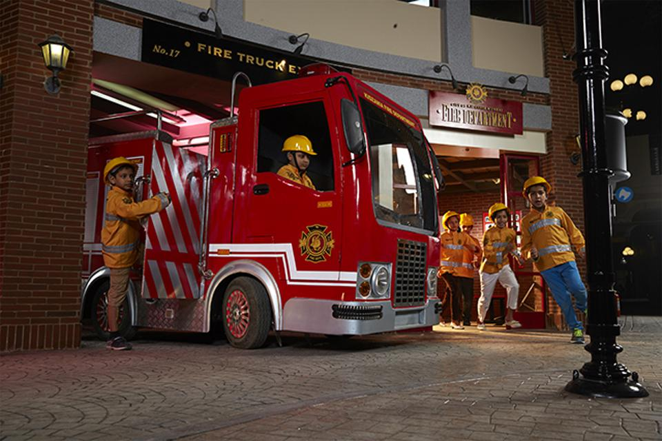 Children role-play as firefighters at one of KidZania's vocational theme parks.