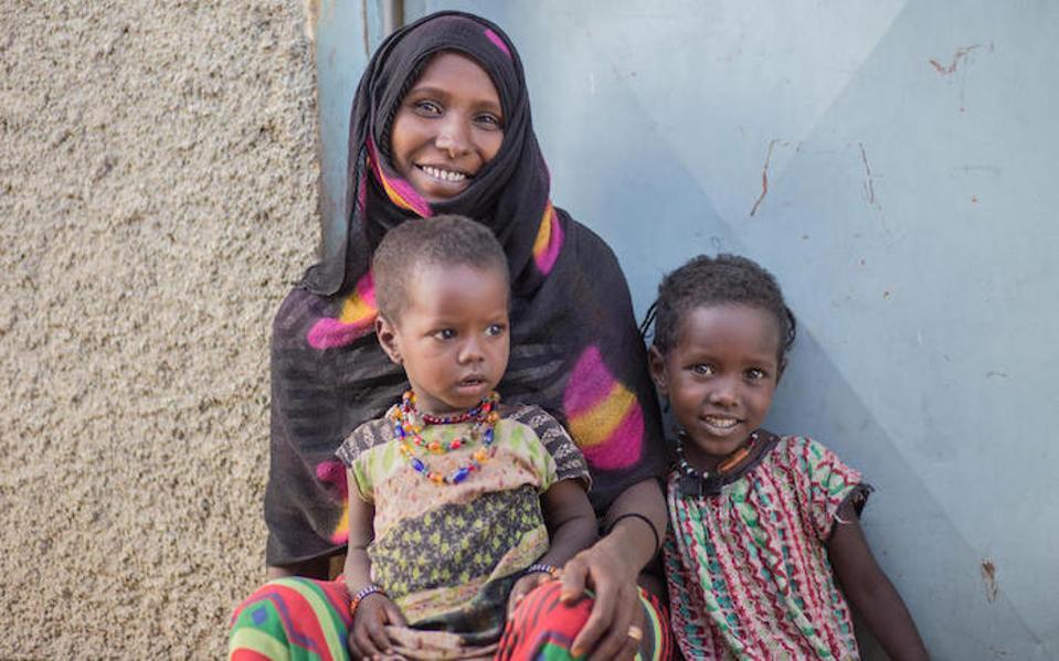 Chifra Woreda está protegiendo a sus hijas Kedija, 2, (en su regazo) y Hawa, 5, de ser sometidas a la mutilación genital femenina en la Región Afar de Etiopía.
