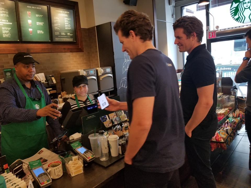 Cameron Winklevoss pays for coffee at Starbucks using a cryptocurrency he and his brother Tyler, looking on, helped create. (May 2, 2019)