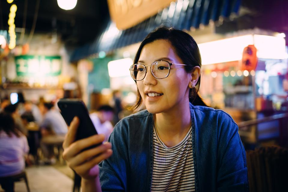 Young woman using smartphone in a traditional style restaurant