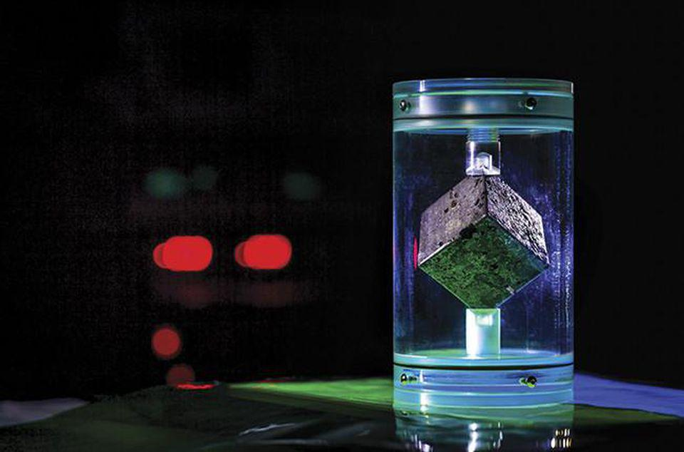 The cube has voids from bubbles, signs of a rough casting process common in early uranium processing.