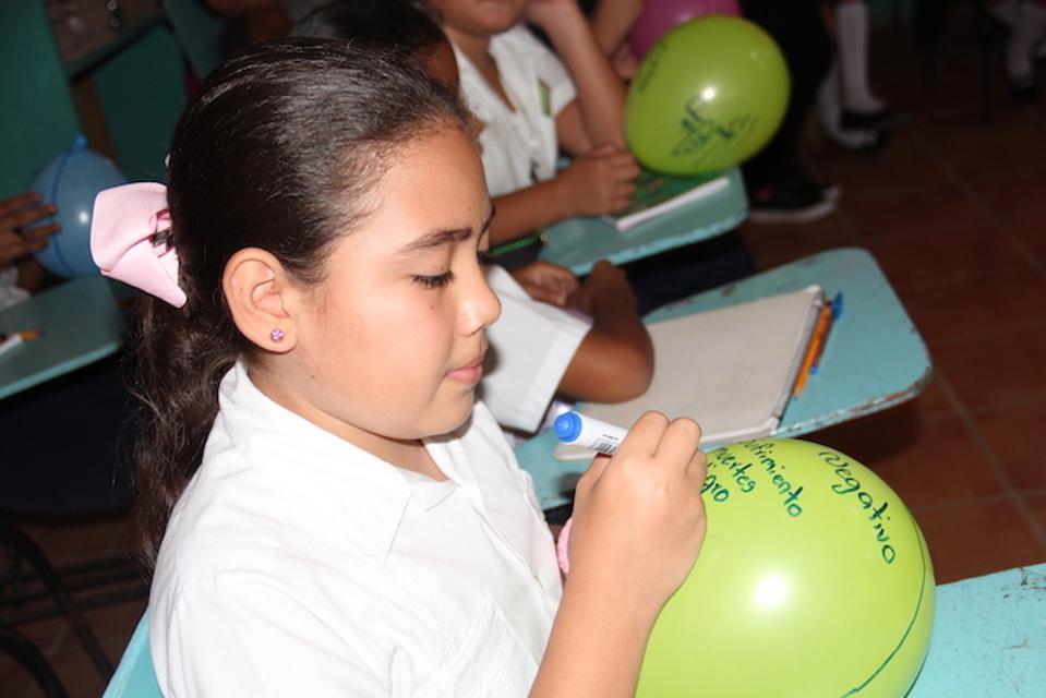 At Escuela Agusto C. Coello in Villanueva, Honduras, children blow into balloons to release their anxieties, then write their worries on the balloons.