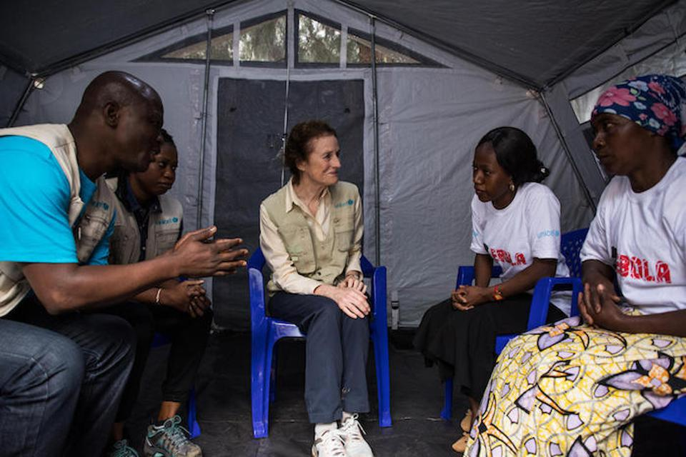On 20 March 2019 in Butembo, Democratic Republic of Congo, UNICEF Executive Director Henrietta H. Fore (center) speaks with Ebola survivors Fabiola Masika Mwengesyali (far right) and Huguette Mulyanza Vthya (black skirt).