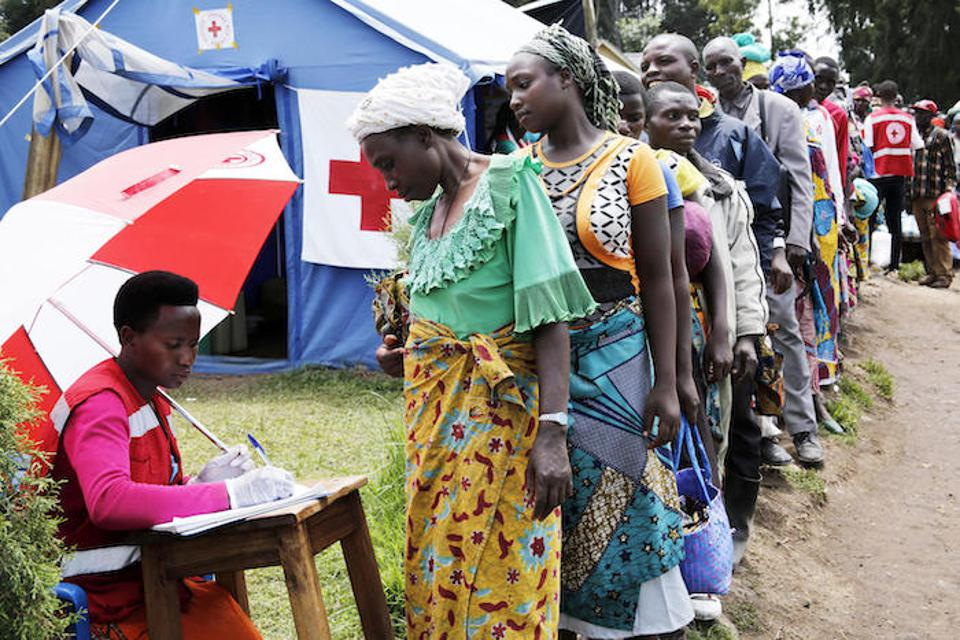 A Uganda Red Cross volunteer registers a woman as new arrivals from DRC line up at a screening facility set up in the border town of Bunangana, Uganda. UNICEF is supporting education and water, sanitation and hygiene interventions in Uganda's Kisoro and Kanungu districts.