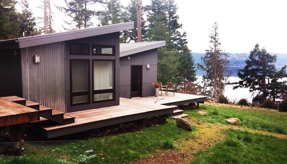 Tiny house on a hill overlooking a lake.