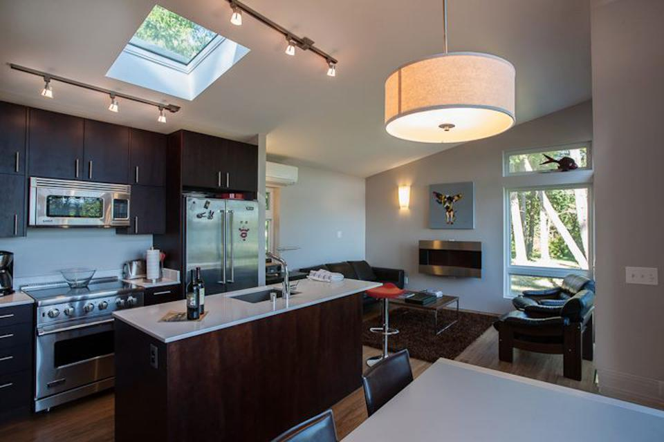Kitchen in a tiny house. Dark cabinets and white countertop and a skylight.