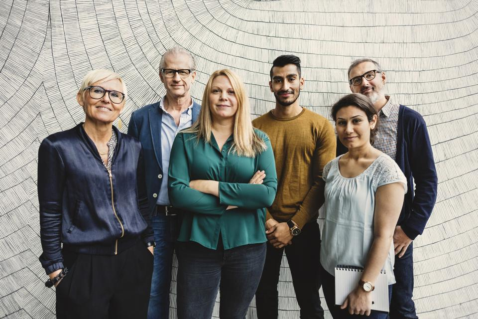 Portrait of confident multi-ethnic business people standing against wall in office